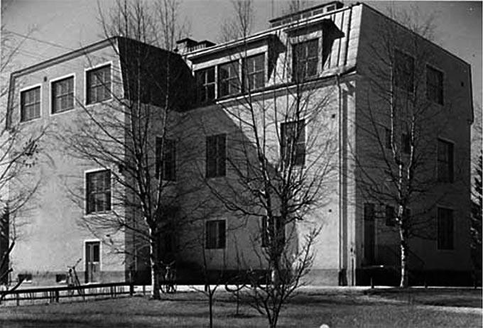 """Bild 7: Folkskolan i Karlholmsbruk 1955. Bilden är hämtad från """"Kommunerna 1955"""", en dokumentation av svenska landskommuner från det tidiga 1950-talet. Den ursprungliga bildtexten lyder: """"Skolan i Karlholmsbruk. År 1920 ansågs skolan i hög grad överdimensionerad. År 1955 är det brist på två lärosalar."""" Karlholm i Västlands kommun hade gott hopp om att få en högstadieskola under 1960-talet, just med tanke på att antalet barn stadigt hade ökat i Västland. Men förhoppningarna grusades. Varken Karlholm eller Skärplinge fick någon högstadieskola under 1960-talet och stenskolan på bilden ovan som en gång i tiden varit modern började nu anses föråldrad. Den blev 1976 ersatt av en nybyggd låg- och mellanstadieskola."""