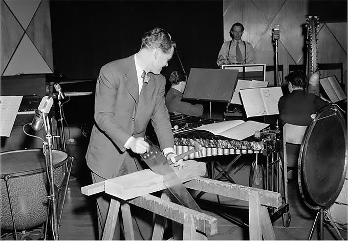 """Anders Soldén sågar efter noter i radioprogrammet """"Man bygger ett hus"""" i skolradion. Källa: Stockholmskällan. Fotonummer SvD 33610, 1953"""