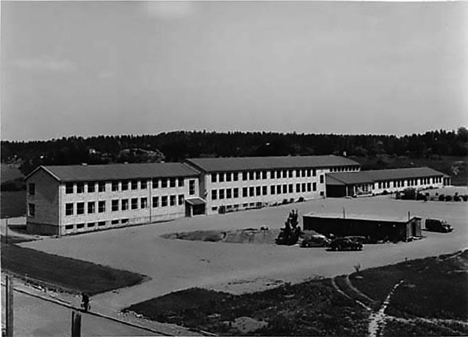 """Bild 1: Österåkers centralskola 1955, sex år efter att den byggts. Österåker var en av de första 14 kommunerna som deltog i enhetsskoleförsöken. Den ljusa tegelskolan som senare bytte namn till Bergaskolan byggdes 2009 om till Österåkers gymnasium. Bilden är hämtad från """"Kommunerna 1955"""", en dokumentation av svenska landskommuner från det tidiga 1950-talet."""